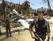 Armed police officers stand guard near the ruins of a nightclub that was flattened by an explosion.
