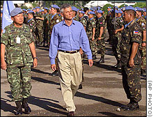 As Chief of UNTAET Sergio Vierra de Mello, center, inspects U.N. peacekeeper troops during his farewell ceremony in Dili, questions remain unanswered about the murdered newsmen