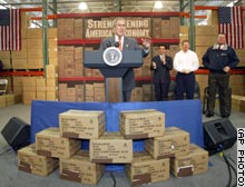 President Bush stands in front of boxes which had