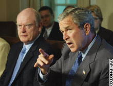 With Secretary of the Treasury John Snow sitting next to him, President Bush talks about Iraq and the economy during a Monday meeting of his Cabinet at the White House.