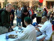 World Wrestling Entertainment (WWE) stars the Hurricane, left, and the Maven sign autographs following a
