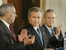 President Bush is applauded by Secretary of State Colin Powell, left, and Defense Secretary Donald Rumsfeld during a signing ceremony for the Iraq and Afghanistan aid package Thursday.