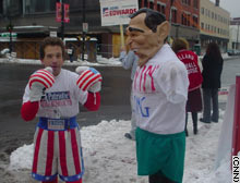 Leslie Gabriel, left, prepares to pound a blow-up bag depicting President Bush in Manchester, New Hampshire.