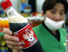 A Shanghai shop assistant shows a Coke bottle featuring Yao Ming's image.