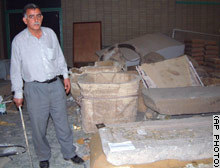 An official at the National Museum of Antiquities, armed with an iron bar, stands guard against looters in Baghdad.