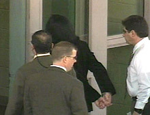 Jackson arrives at the jail in handcuffs after surrendering to police.