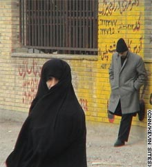 An Iranian woman in full cover stands by the road.