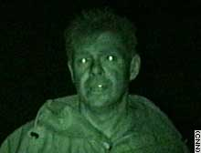 CNN's Martin Savidge reports using a night scope, which reflects in his eyes.