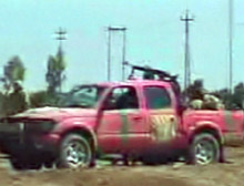 A group of Iraqis taken prisoner were driving a pink pickup truck with a machine gun mounted on it.