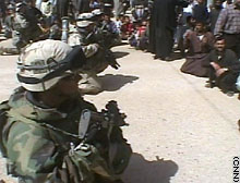 U.S. soldiers kneel and lower their weapons, a gesture to show they mean no threat; some in the crowd follow suit and sit down.