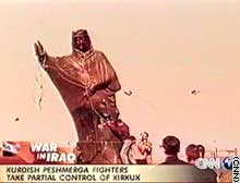 The statue of Saddam in tribal clothes topples in Kirkuk.
