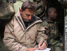 CNN correspondent Alessio Vinci takes notes while Lance Cpl. Marques Morris of Albany, Georgia, rests inside an amphibious assault vehicle in Iraq.