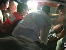 Palestinian rescue workers unload an injured man from an ambulance after Sunday's rocket attack in Gaza.