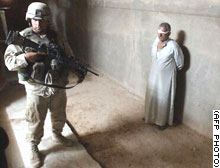 An Iraqi man is kept under guard after the raids.