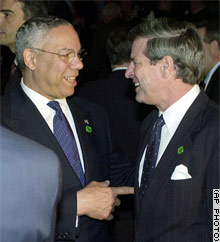 U.S. Secretary of State Colin Powell and L. Paul Bremer, the U.S. civilian administrator for Iraq, talk at a session of the International Donors' Conference in Madrid on Thursday.