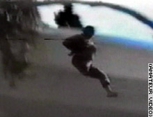 Members of the Fedayeen Saddam throw a bound man from a rooftop. This man, and others shown on the videotape, survived the fall.