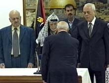 Palestinian Prime Minister Ahmed Qorei faces Arafat during his government's swearing in ceremony.