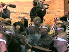 Reporters don 3-D glasses to see a multi-dimentional image of Mars sent back by the rover.