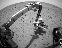 The Spirit rover reaches for Martian soil for the first time.